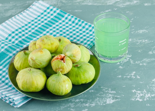 Green figs with drink in a plate on plaster and picnic cloth, top view.