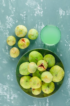 Green figs with drink in a plate on plaster wall, top view.