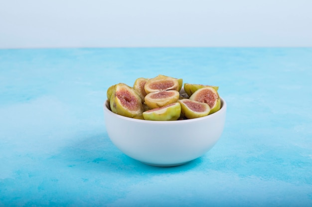 Green figs with red seeds in a white ceramic bowl on blue.