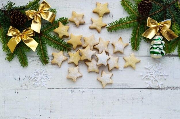 Зеленые еловые ветки и украшение с золотыми бантами и звездным печеньем на белом фоне