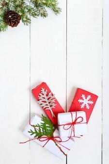 Зеленые еловые ветки и небольшие подарочные коробки