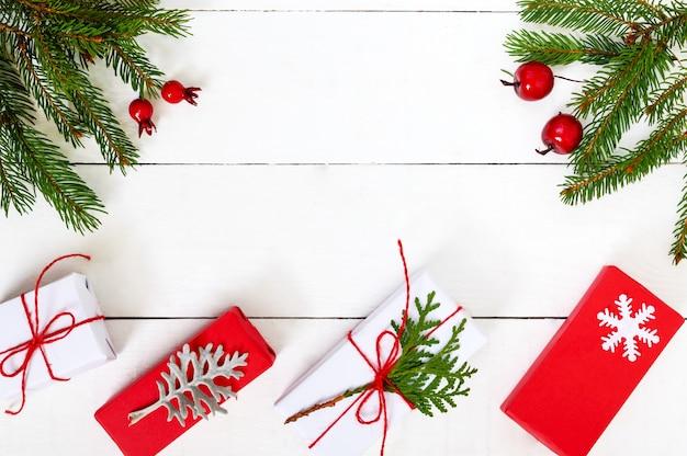 Зеленые еловые ветки, декоративные ягоды и подарочные коробки