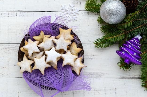 Зеленые еловые ветки с звездным печеньем на белом фоне. рождественская тема. вид сверху.