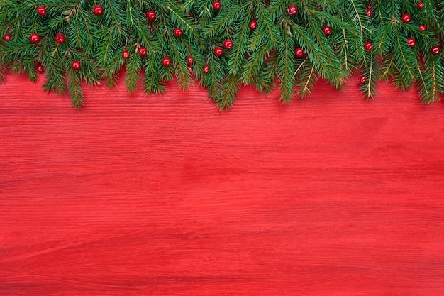 빨간 나무 표면에 녹색 전나무 나무 가지.