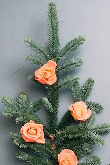 Зеленая веточка ели, украшенная бутонами персиковой розы