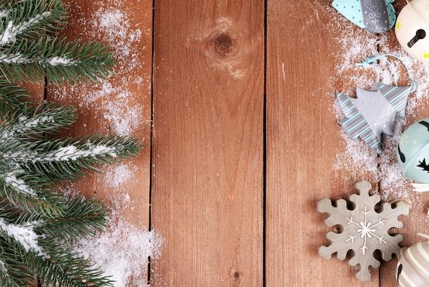 木製の背景におもちゃと雪と緑のモミの木