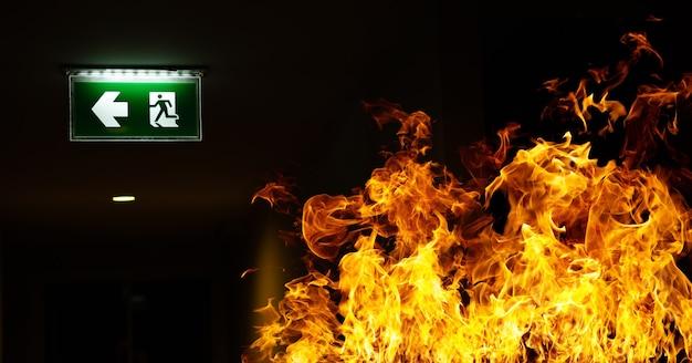 녹색 화재 탈출 기호가 창고의 천장에 매달려 있습니다.