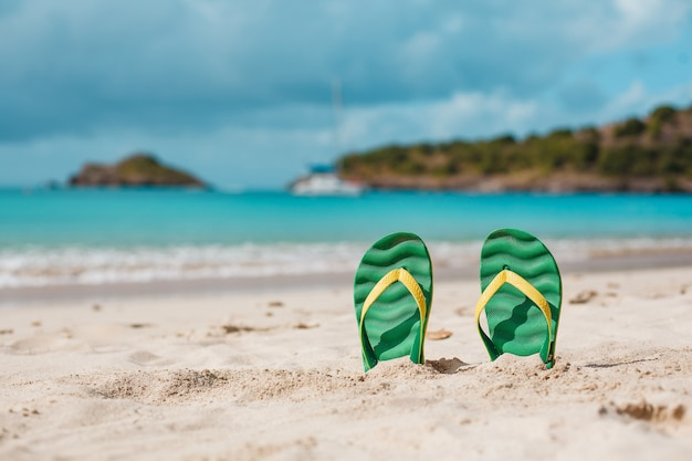 Green flip flops in the white sandy beach near sea waves. summer vacation concept