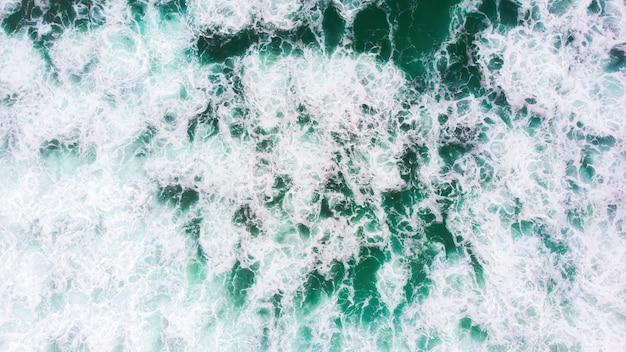 Зеленые пенящиеся волны на северном пляже в назаре, португалия