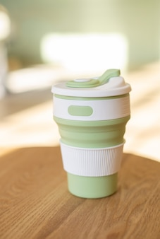Green foldable silicone cup for drinks without plastic in the style of zero waste on a interior room, close-up