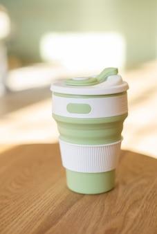 緑の折りたたみ式シリコンカップ、プラスチックなしのドリンク用、室内の廃棄物ゼロのスタイル、クローズアップ