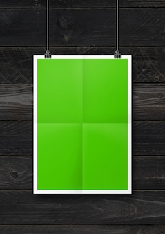 Green folded poster hanging on a black wooden wall with clips. blank mockup template