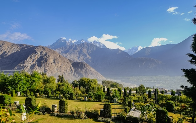 Green foliage in summer against karakoram mountain range with morning fog in the city.