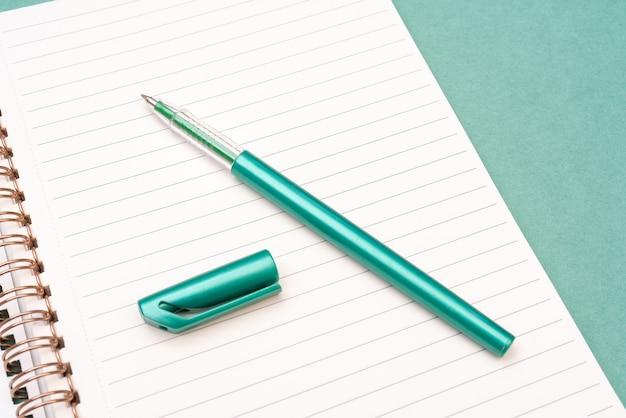 緑の万年筆とメモ帳のページ。奨学金と教育の準備。創造性の苦痛。