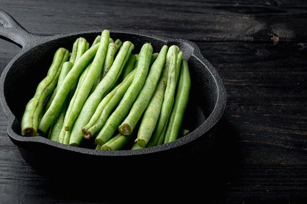 녹색 프랑스 콩 요리 세트, 검은 나무 테이블에 주철 팬 프라이팬