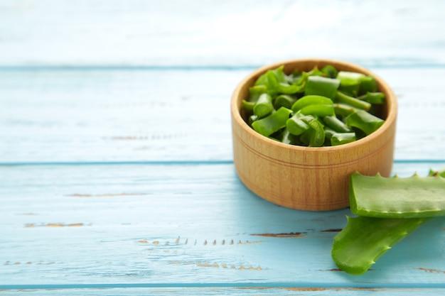 Зеленый свежий лист алоэ вера в деревянной миске на синем фоне. натуральные лечебные травы, уход за кожей, спа-концепция здоровья и красоты. вид сверху