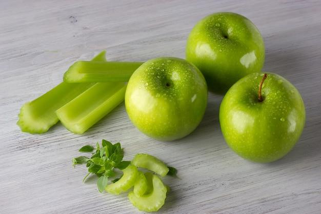 緑の新鮮なリンゴ、セロリのスライス、木製のテーブルにいくつかのバジルの葉