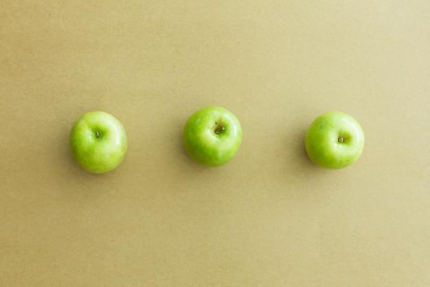Зеленые свежие яблоки на бумажном фоне