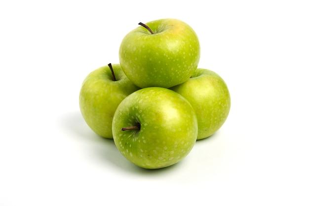 Зеленые свежие яблоки на белом фоне.