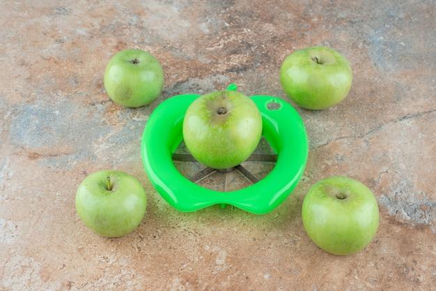 Зеленые свежие яблоки с инструментом для очистки на мраморном столе.