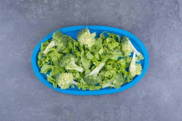 Зеленая свежая брокколи, изолированная на синей поверхности