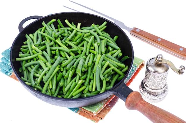 フライパンで緑の新鮮な緑の豆。スタジオ写真