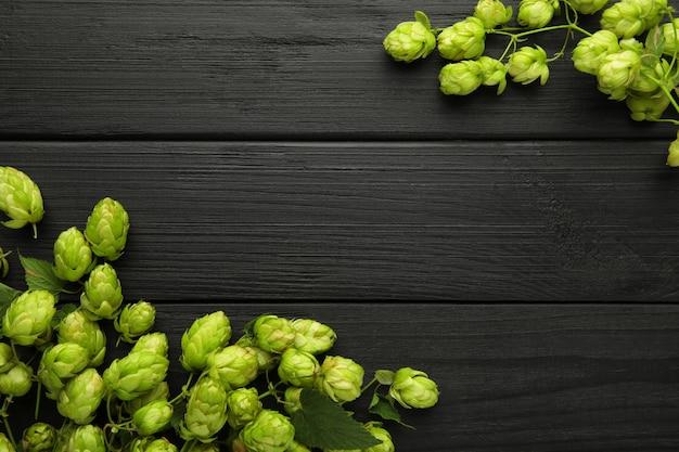 Зеленые свежие шишки хмеля для приготовления пива и хлеба на черном фоне. вид сверху