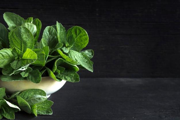 スペースのコピーと黒い木製のテーブルの上の緑の新鮮なミント。