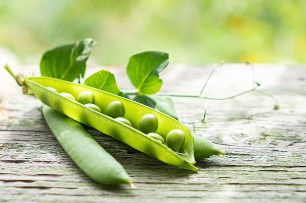 庭の屋外の木製の机の上の緑の新鮮な熟したエンドウ豆の鞘。
