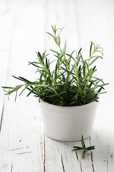 Green fresh rosemary on the wooden table