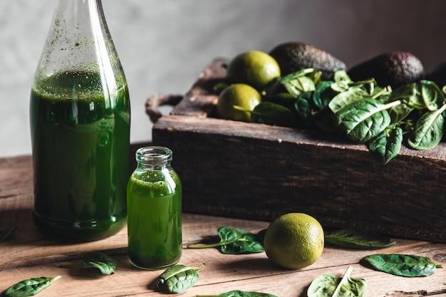 古い木製の箱、暗い背景、上面図の果物、緑、野菜と瓶の緑の新鮮なスムージー。デトックス、ダイエット、きれいな食事、ベジタリアン、ビーガン、フィットネス、健康的なライフスタイルの概念