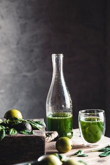 Green fresh smoothie in jar with fruit, greens and vegetables in old wooden box, dark background, top view. detox, dieting, clean eating, vegetarian, vegan, fitness, healthy lifestyle concept