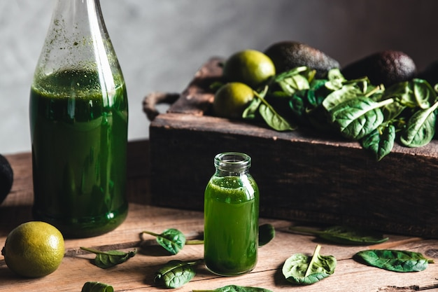 Green fresh smoothie in jar with fruit, greens and vegetables in old wooden box