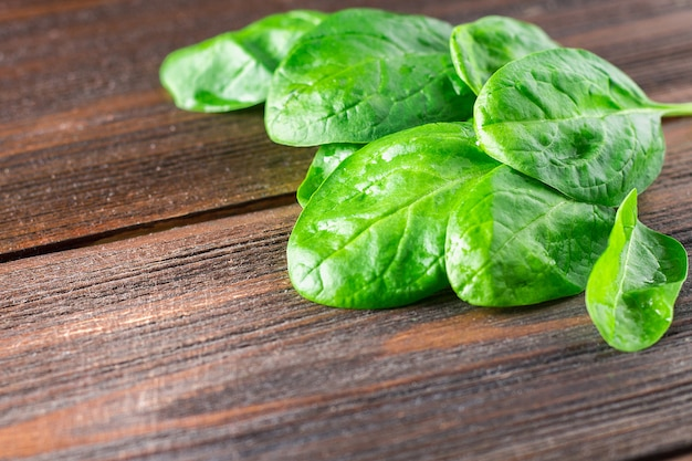 Green fresh spinach leaves on a wooden table.