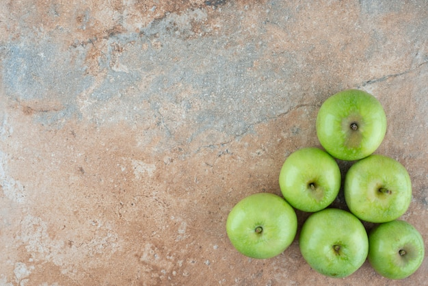 Green fresh sweet apples on marble table.