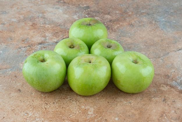 Зеленые свежие сладкие яблоки на мраморном столе.