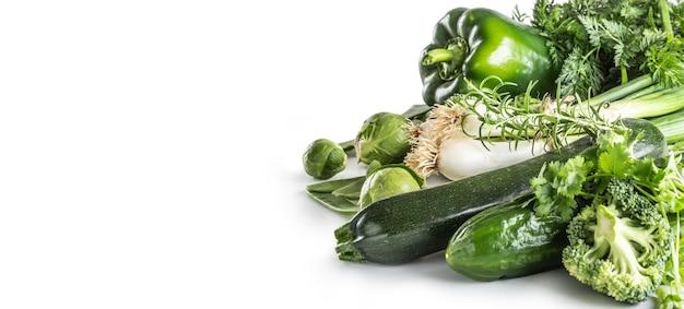 白い背景で隔離の緑の新鮮な野菜。タマネギきゅうりエンドウ豆ブロッコリーズッキーニと他の健康野菜。