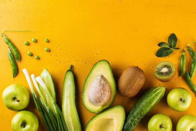 Зеленые свежие овощи и фрукты на желтом