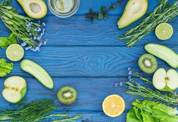 青い木製のテーブルの上の緑の新鮮な野菜とスパイス。上面図。テキストの場所