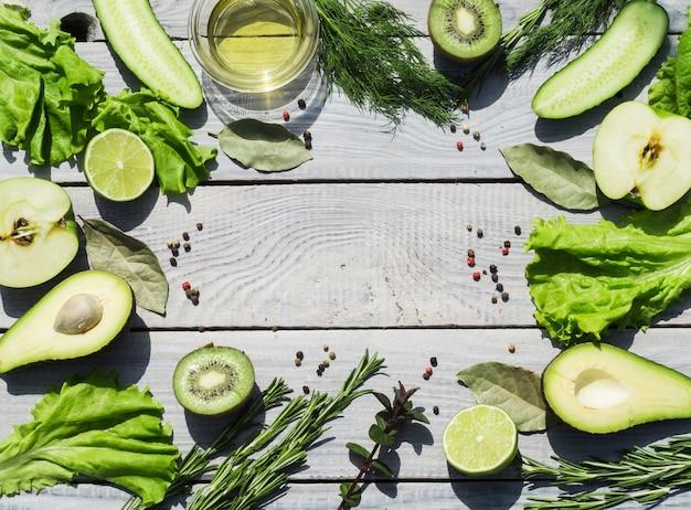 白い木製のテーブルの上の緑の新鮮な野菜とスパイス。上面図。テキストの場所