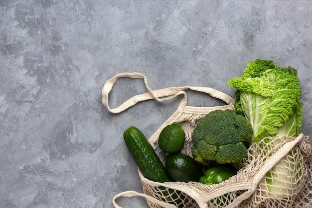 灰色の背景にひもの袋に緑の新鮮な野菜