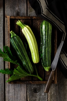Green fresh zucchini on an old wooden surface