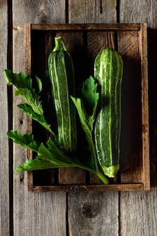 Зеленые свежие кабачки на старой деревянной поверхности