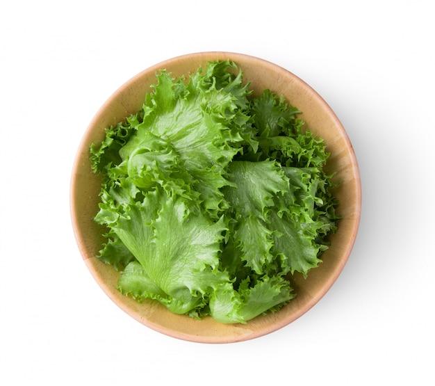 흰 벽에 나무 그릇에 녹색 frillies 빙산 양상추.