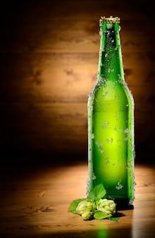 ビールの緑の冷凍ボトルと木にホップ