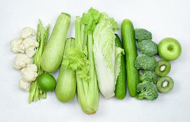 밝은 배경에 쌓인 녹색 과일과 야채