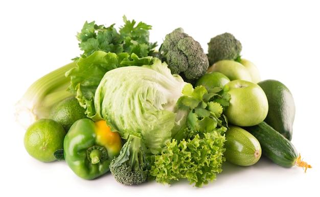 Зеленые фрукты и овощи на белой поверхности.