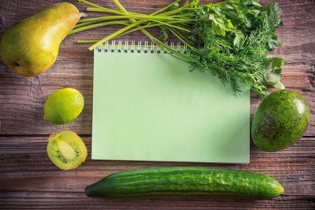 Зеленые фрукты и овощи на деревянном фоне