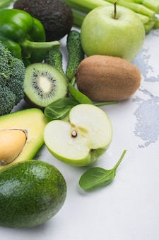 Green fruits and vegetables on white