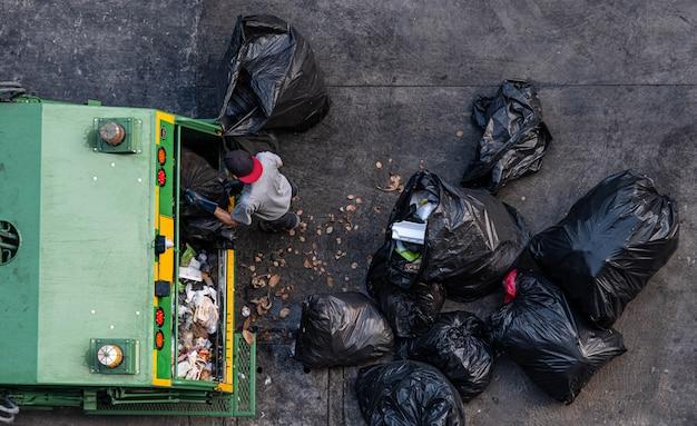 녹색 쓰레기 트럭 직원들이 검은 쓰레기 봉투를 많이 모으고 있습니다